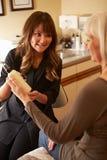 劝告的美容师美容品的女性客户 库存照片