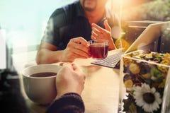 办公室与坐chattin的两个设计师同事的咖啡休息 免版税库存照片
