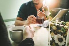 办公室与坐chattin的两个设计师同事的咖啡休息 库存图片