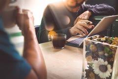 办公室与坐chattin的两个设计师同事的咖啡休息 库存照片