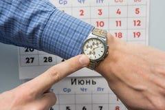办公室专家递点到一块手表,在背景中是挂历 库存图片