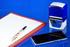 办公室会计桌面,蓝色背景,与必要的辅助部件 与文件的文件夹,智能手机通信装置为 库存图片