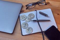办公室便携式的工作区域银币Bitcoin膝上型计算机手机玻璃、笔记本和文字笔 Bitcoin Cryptocur的概念 图库摄影