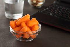 办公室午餐的健康快餐:嫩胡萝卜、杏仁、腰果和杯水 库存照片