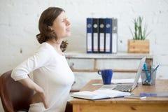 年轻办公室妇女感觉腰疼 免版税库存图片