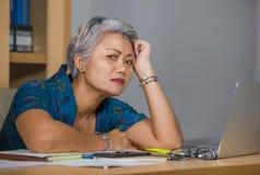 办公室工作在手提电脑书桌上的哀伤和沮丧的成熟可爱的亚裔妇女生活方式画象被注重和疲乏 图库摄影