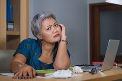 办公室工作在手提电脑书桌上的哀伤和沮丧的成熟可爱的亚裔妇女生活方式画象被注重和疲乏 免版税图库摄影