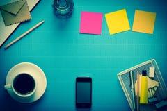 办公室工作场所、办公设备和咖啡休息在蓝色绉纱 库存图片