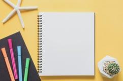 办公室工作场所最小的概念 有海星的空白的笔记本 免版税库存照片
