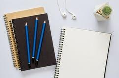 办公室工作场所概念 笔记本、仙人掌、耳机和铅笔 库存照片