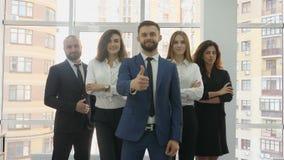 办公室工作者、两个年轻人和三个少妇在三角排队,并且前景的一个年轻人显示a 股票视频