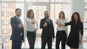 办公室工作者、两个年轻人和三个少妇有骄傲地被抬的头的显示类并且微笑看框架 股票视频