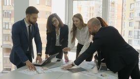 办公室工作者、公司的一个年轻队,两个男人和三名妇女谈论设施文件开发为 股票视频