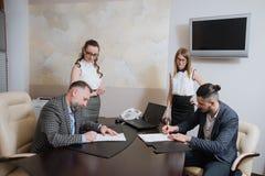 办公室工作者做成交,签署关于合作的协议 免版税库存照片
