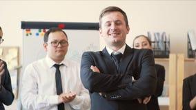 办公室工作者在上司后站在队中并且拍他们的手,与在他的胸口交叉的他的双臂的上司立场 股票视频