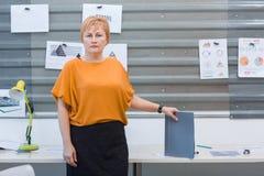 办公室工作者妇女在与一个文件夹的一张桌附近站立在她的手上 在办公室里面 库存照片