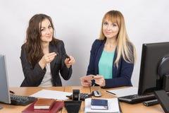 办公室工作者显示同事染睫毛油在您的书桌 免版税库存照片