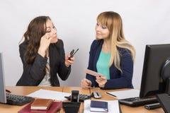 办公室工作者生气蓬勃谈话关于化妆用品在您的书桌 库存照片