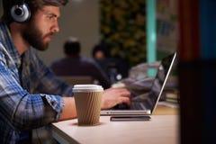 办公室工作者用在后研究膝上型计算机的书桌的咖啡 图库摄影