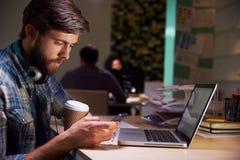 办公室工作者用在后研究膝上型计算机的书桌的咖啡 免版税图库摄影