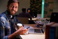 办公室工作者用在后研究膝上型计算机的书桌的咖啡 免版税库存照片