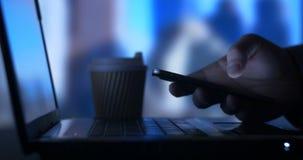 办公室工作者键入在膝上型计算机的企业人检查手机在办公室 股票录像