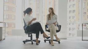 办公室工作者,两名妇女坐椅子谈话,其中一名妇女告诉一个滑稽可笑的故事其他笑 股票录像
