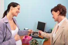 办公室怀孕的显示的超声波工作者 免版税库存图片