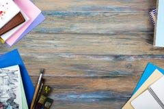 办公室有供应的桌书桌,白色空白的笔记本,杯子,笔,个人计算机,弄皱了纸,在木背景的花 顶层 免版税库存照片