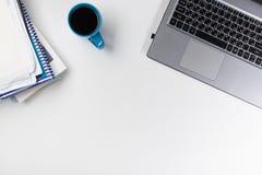 办公室有供应的桌书桌,空白的笔记本,杯子,笔,个人计算机,弄皱了纸,在白色背景的花 顶视图 免版税库存图片