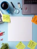 办公室有供应的桌书桌,空白的笔记本,杯子,笔,个人计算机,弄皱了纸,在蓝色背景的花 顶视图 免版税库存照片