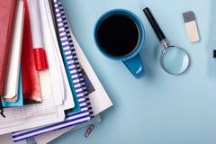 办公室有供应的桌书桌,空白的笔记本,杯子,笔,个人计算机,弄皱了纸,在蓝色背景的花 顶视图 库存照片