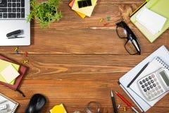 办公室有套的五颜六色的供应,白色空白的笔记本,杯子,笔,个人计算机桌书桌,弄皱了纸,在木的花 免版税库存图片