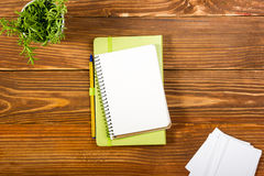 办公室有套的五颜六色的供应,白色空白的笔记本,杯子,笔,个人计算机桌书桌,弄皱了纸,在木的花 库存照片