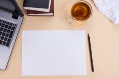 办公室有套的五颜六色的供应,白色空白的笔记本,杯子,笔,个人计算机桌书桌,弄皱了纸,在灰棕色的花 库存照片