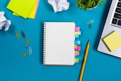 办公室有套的五颜六色的供应,白色空白的笔记本,杯子,笔,个人计算机桌书桌,弄皱了纸,在蓝色的花 库存照片