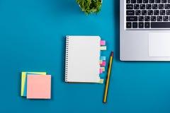 办公室有套的五颜六色的供应,白色空白的笔记本,杯子,笔,个人计算机桌书桌,弄皱了纸,在蓝色的花 免版税库存图片