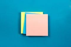 办公室有套的五颜六色的供应,白色空白的笔记本,杯子,笔,个人计算机桌书桌,弄皱了纸,在蓝色的花 免版税库存照片