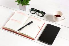 办公室有套的供应,白色空白的笔记薄,杯子,笔,片剂,玻璃,在白色背景的花桌书桌 顶层 免版税图库摄影