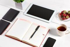 办公室有套的供应,白色空白的笔记薄,杯子,笔,片剂,玻璃,在白色背景的花桌书桌 顶层 免版税库存图片