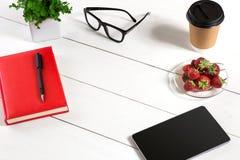 办公室有套的供应,红色笔记薄,杯子,笔,片剂,玻璃,在白色背景的花桌书桌 顶视图 库存照片