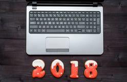 办公室有开放膝上型计算机的桌书桌顶视图和新年2018签署从姜饼曲奇饼的标志 企业假日概念 免版税库存照片