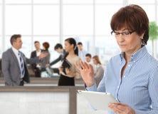 办公室有片剂的生活女实业家 免版税库存图片