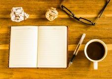 办公室木头桌 笔记薄,放大镜,玻璃,笔 免版税库存图片