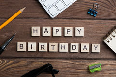 办公室材料和木立方体在工作场所制表做生日快乐词组 库存照片