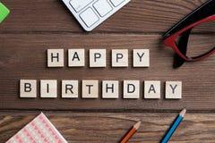 办公室材料和木立方体在工作场所制表做生日快乐词组 免版税图库摄影