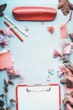 办公室桌书桌顶视图  与笔、剪贴板、辅助部件和花的工作区在蓝色背景 免版税库存照片