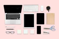 办公室桌平的位置照片与便携式计算机、数字式片剂、手机和辅助部件的 在现代背景 桌面o 库存图片
