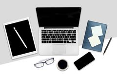 办公室桌平的位置照片与便携式计算机、数字式片剂、手机和辅助部件的 在现代背景 桌面o 库存照片