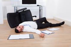 从办公室椅子下落的商人 免版税图库摄影